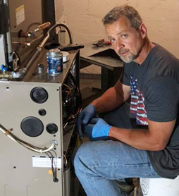 Tim gordon working on an heating unit with blue gloves on