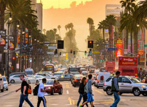 a city in california with hazy setting, a busy street, pedestrians walking to and fro, and palm trees in the background