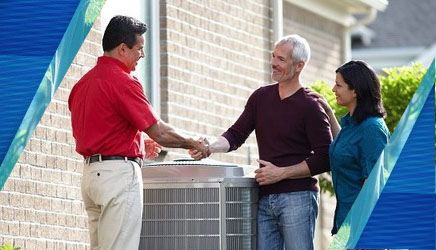 a red technician shaking the hand of a man with his wife in front of an air conditioning unit